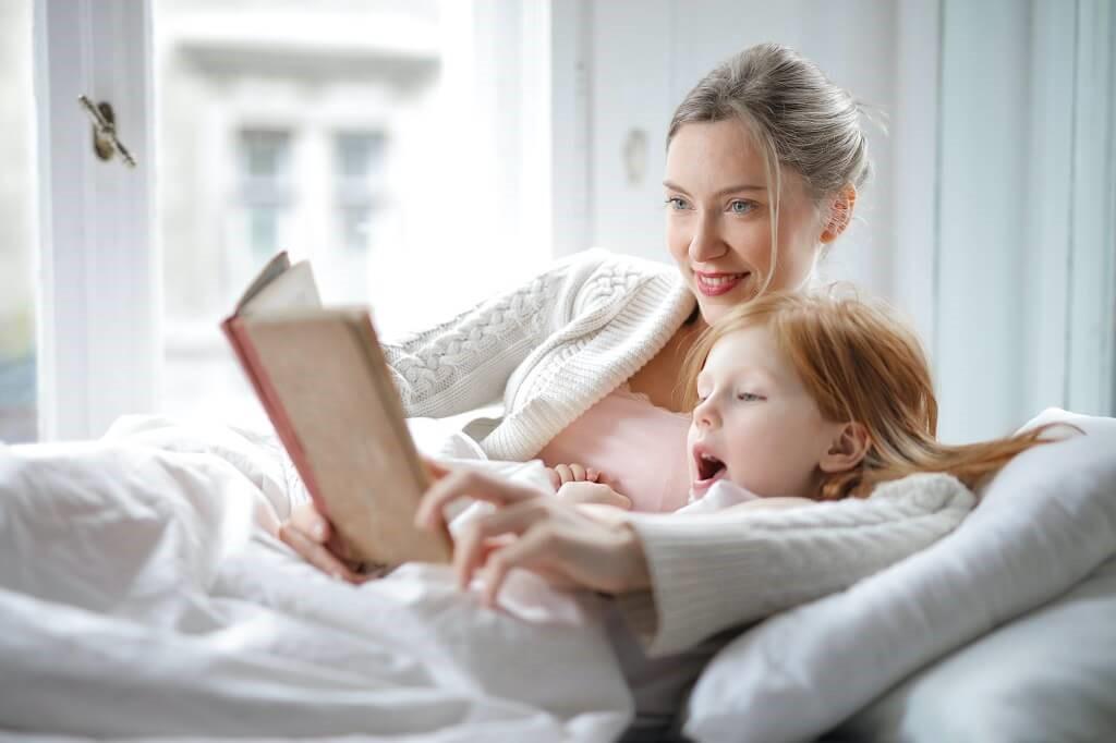 Майка чете книга на дъщеря си